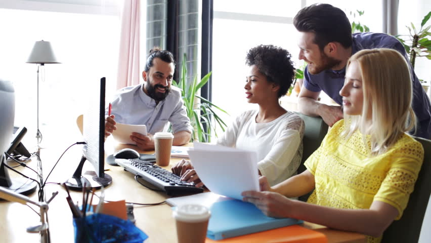 Business, startup and people concept - happy creative team with computers and folder discussing project in office   Shutterstock HD Video #9870797