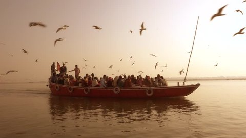 Tourist Boat and Seagulls, Ganges River, Varanasi, India, february 2015.Indian tourists taking the popular boat tour on the sacred Ganges river in Varanasi.