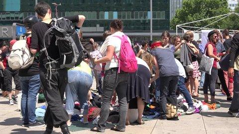 BERLIN- GERMANY, JULY 3, 2014, ULTRA HD 4K People buy old clothe on market street in public square by day
