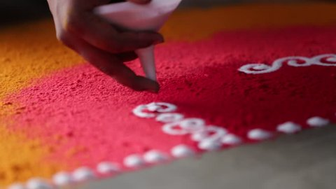 Rangoli with coloured powder being created by Rangoli artist on occasion of Hindu Wedding, Mumbai, Maharashtra, India.