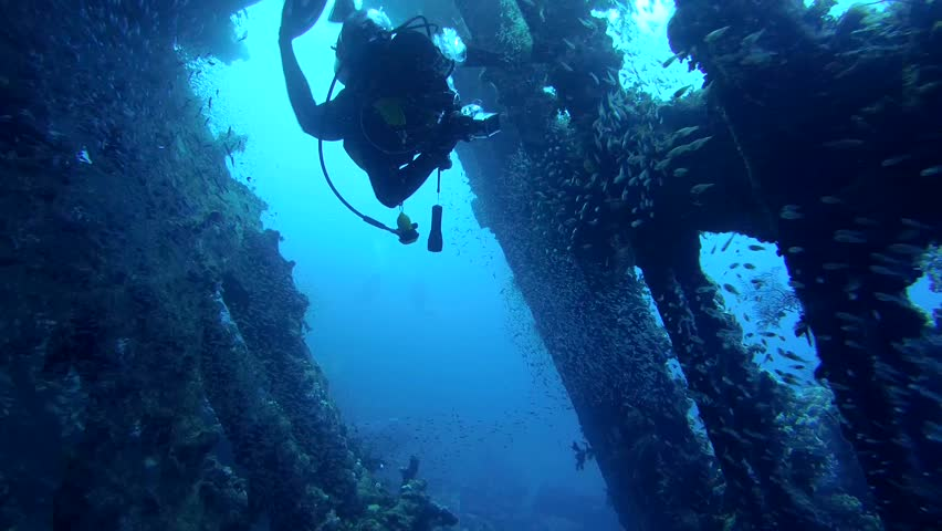 STRAIT OF GUBAL, RED SEA, EGYPT - OCTOBER, 2014: A diver swims inside wrecked ship SS Carnatic, Red Sea, Egypt