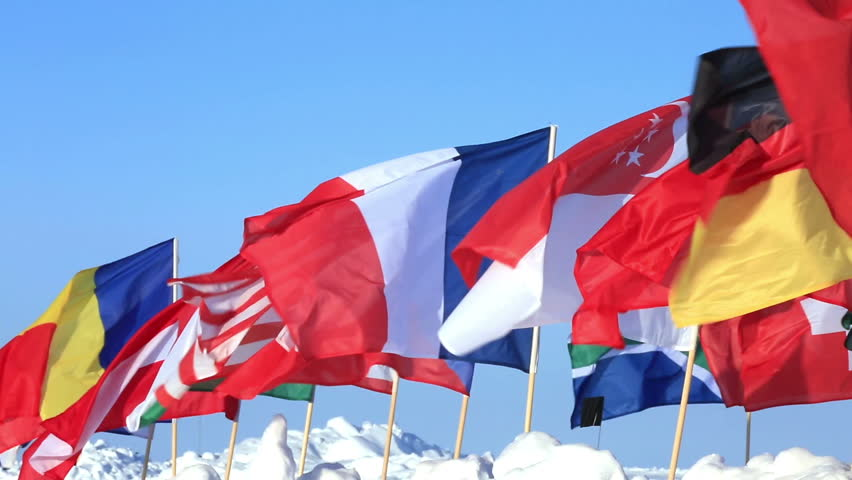 Lots of flags of different countries fluttering in the wind.