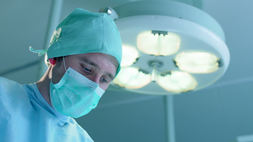 Closeup shot of male surgeon performing an operation. His assistant wipes sweat drops from his forehead using gauze pad.