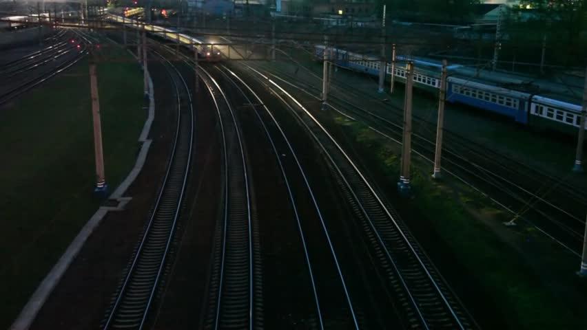 suburban electric train moving on night railway near station