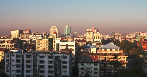 Panoramic view of Yangon, Myanmar at sunrise with moving shadows and sun light on buildings and rooftops because of rising sun. Time lapse video