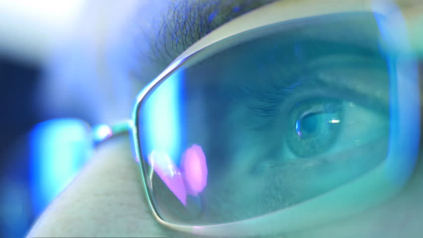 Reflection in the eye and glasses of the monitor screen when watching an action movie. Close up. Shallow depth of field #9940301
