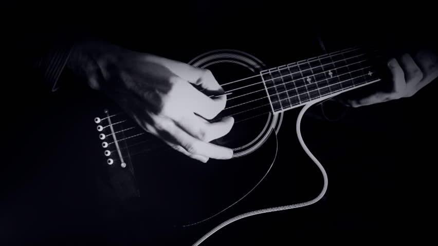 Noir style, man plays on guitar with a low-key black-and-white visual style.