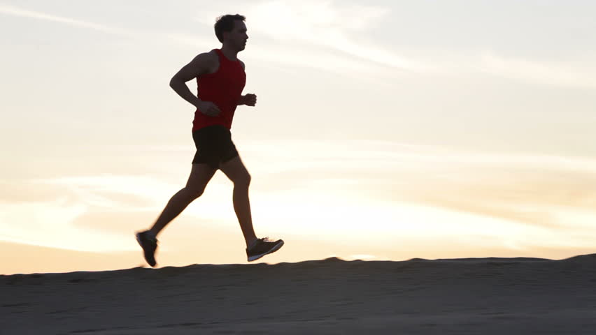 Jogging runner man running at sunset. Male jogger training for marathon run running in silhouette against colorful yellow sky. Fit fitness model living healthy active outdoor lifestyle. | Shutterstock HD Video #9976991